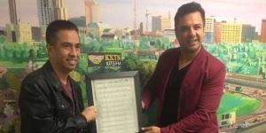"""KXTN Program Director Mark Arias receives a copy of original song notes for """"Las Nubes"""" from Tortilla Factory's Alfredo Guerrero. (Courtesy photo)"""